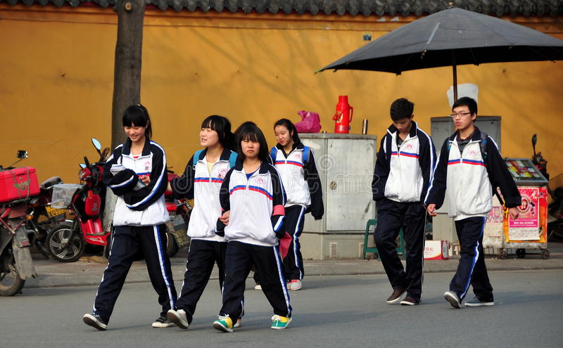 Pengzhou China: High School Students. A group of Chinese high school students wearing their regulation blue and white jackets walking home after classes end for stock photo