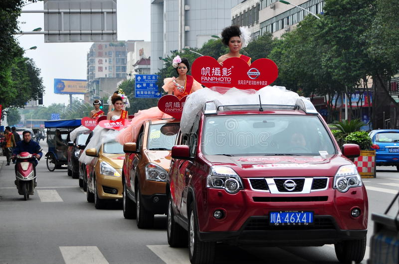 Pengzhou, China: Models Riding in Cars. Models in wedding apparel pose atop a fleet of Nissan cars during a promotion by Fan Photo, a wedding photography company royalty free stock photography