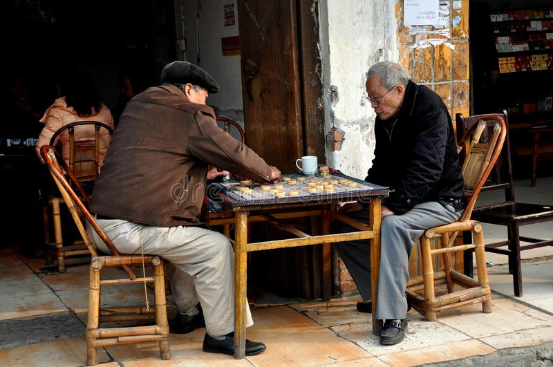 Pengzhou, China: Two Elderly Men Playing Checkers. Two elderly Chinese men sitting in front of a shop playing a game of checkers in Pengzhou, China stock images