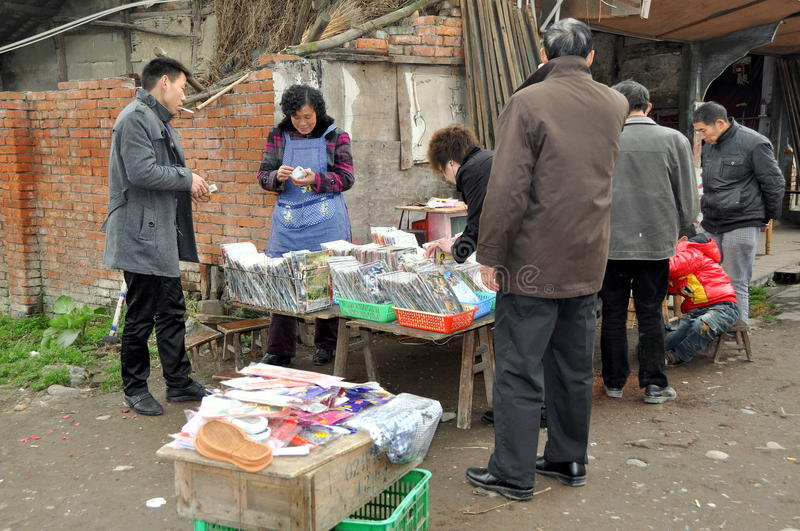 Pengzhou, China: Woman Selling DVD films. Woman gives change to a customer while other people browse through bins of Chinese CD's and DVD films at her small royalty free stock photography