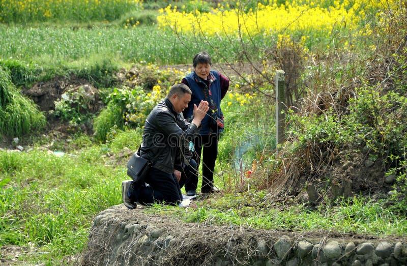 Pengzhou, Chine : Famille priant au tombeau photo libre de droits