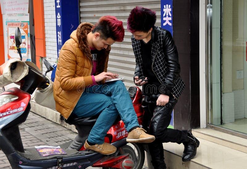 Pengzhou, Chiny: Wieki dojrzewania Sprawdza Ich telefony komórkowych zdjęcie royalty free