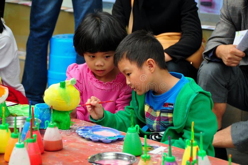 Pengzhou Kina: Barn som målar statyetten royaltyfri foto