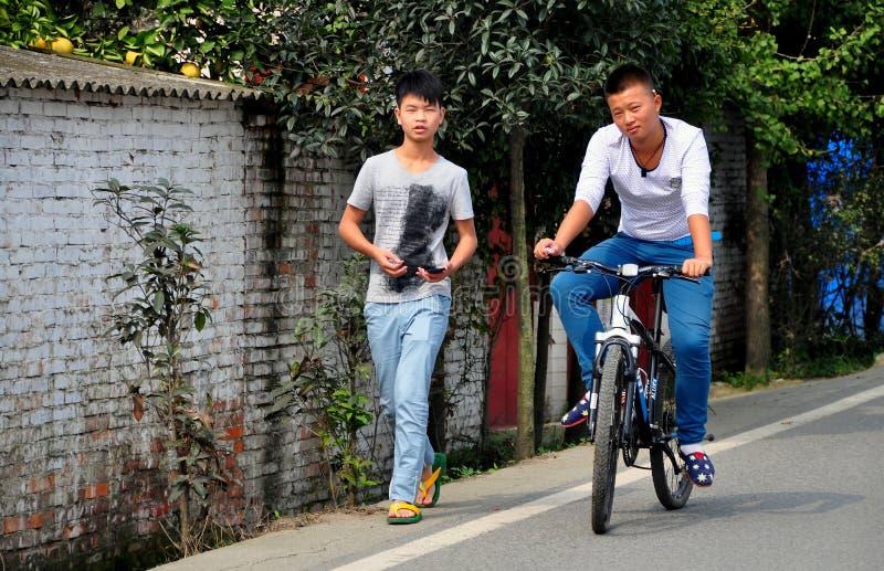 Pengzhou Kina: Unga kinesiska vänner på landsvägen royaltyfri foto