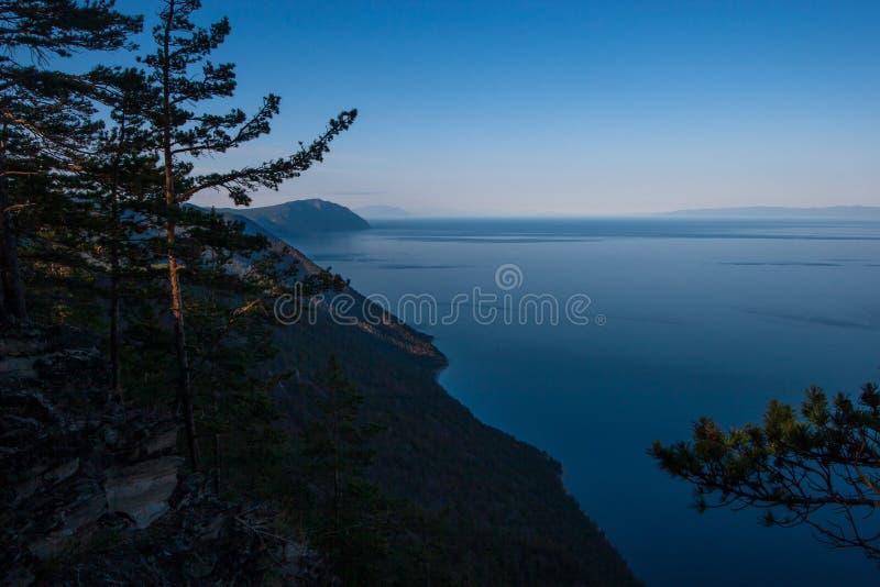 Penhasco alto na costa do Lago Baikal da zona leste na noite No horizonte uma tira das montanhas fotografia de stock