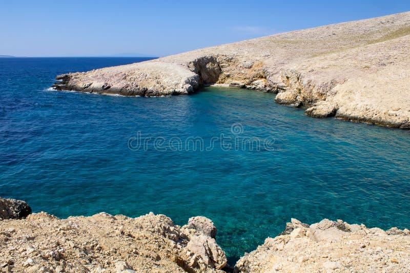 Penhasco no mar com praia pequena e o céu azul, ilha Krk, Croácia fotos de stock royalty free