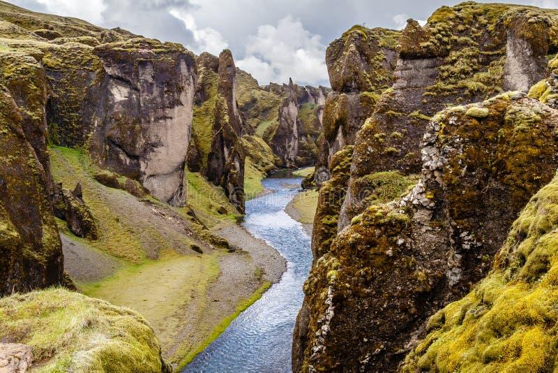 Penhascos íngremes da garganta de Fjadrargljufur e águas do rio de Fjadra, s foto de stock
