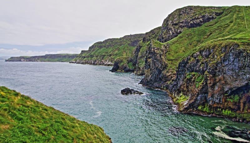Penhascos ao longo da costa irlandesa ao lado da ilha minúscula de Carrick-a-rede foto de stock royalty free
