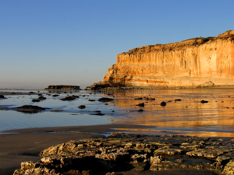 Penhascos com reflexões da noite na praia de estado dos pinhos de Torrey, La Jolla, Califórnia imagens de stock
