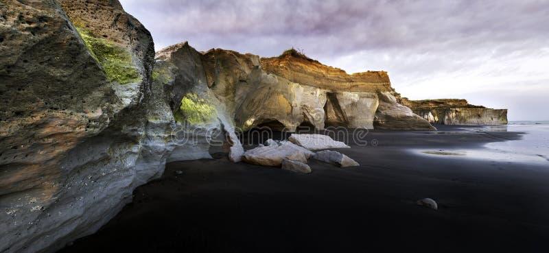 Penhascos da areia do preto de Nova Zelândia fotografia de stock
