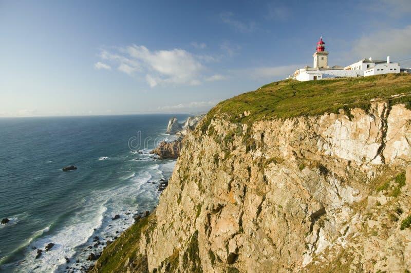 Penhascos e farol de Cabo a Dinamarca Roca no Oceano Atlântico em Sintra, Portugal, o ponto westernmost no continente de Europa, foto de stock