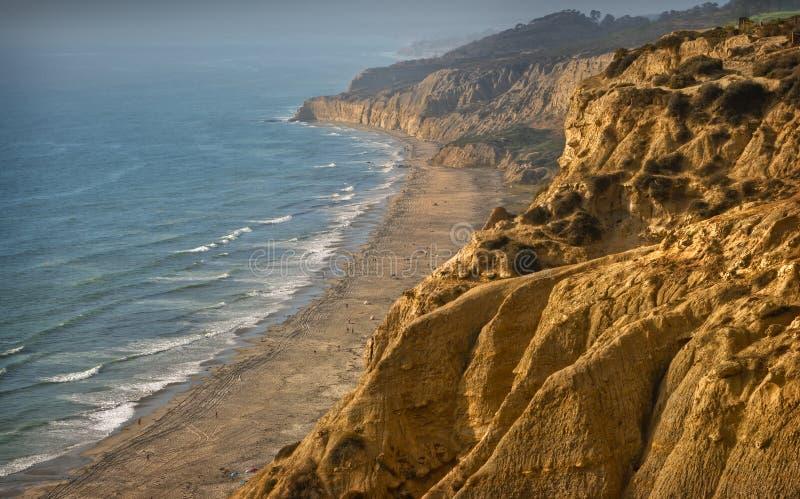 Penhascos e praia no por do sol imagem de stock royalty free