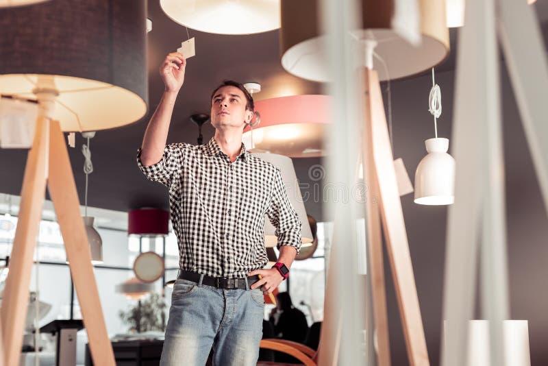 Penibler attraktiver Kunde, der die Preise auf Lampe im Speicher überprüft stockbilder