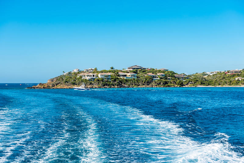Peninsula of St. Thomas island out into the Caribbean se. A with small boat. View off the back of the boat with boat wake royalty free stock photos