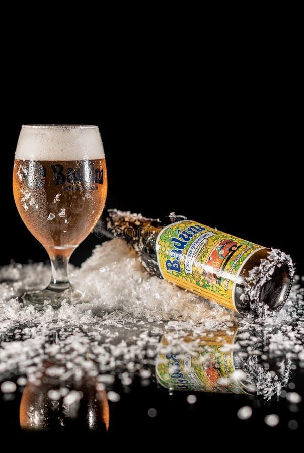 Peniscola, Castellon, Spanien, am 8. Mai 2019: Kaltes geschmackvolles und Schaumbier in einem Bierglas und in einer Badum-Flasche lizenzfreies stockbild