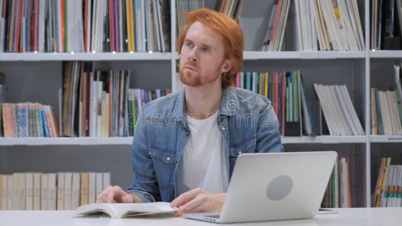 Penisve rudzielec mężczyzna Czytelnicza książka przy pracą obraz royalty free
