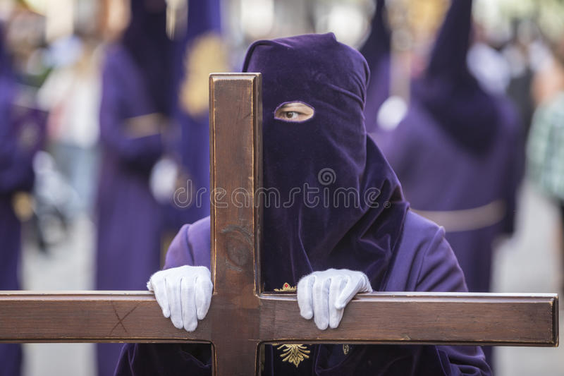 Penitent dressed in purple tunic of velvet resting on wooden cross during atonement station on Holy Week, Andalusia, Spain stock photography