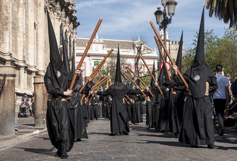 Penitente con su semana cruzada, santa en la fraternidad del Nazarene de Sevilla de estudiantes imagenes de archivo