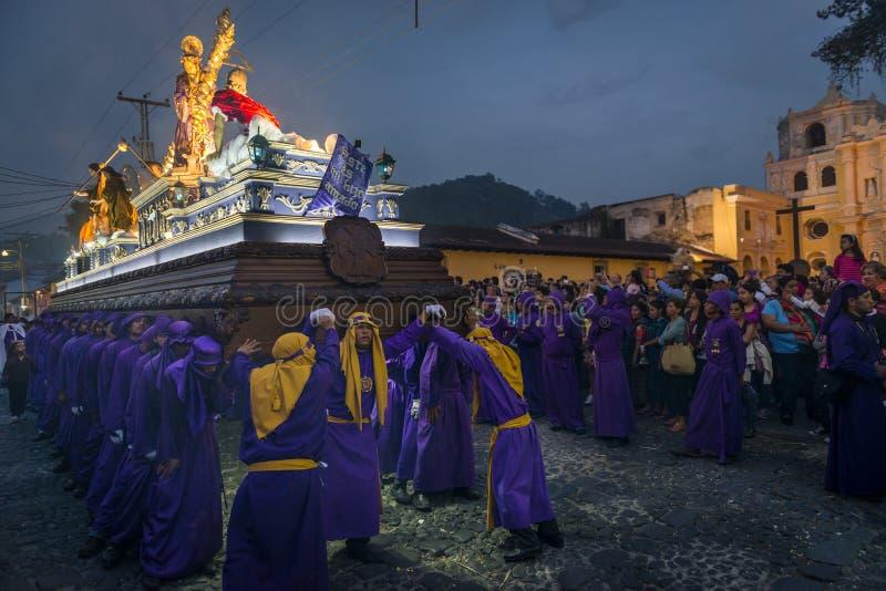 Penitents, die ein Floss mit dem Bild von Jesus Christ in einer Ostern-Prozession nachts während der Karwoche in Antigua, Guatem  stockfotografie