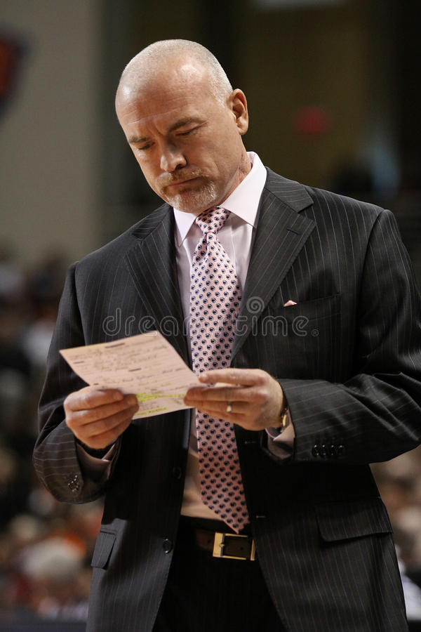 Penn State's Coach Pat Chambers looks at his notes. LEWISBURG, PA. – NOVEMBER 28: Penn State's Coach Pat Chambers looks at his notes during a basketball stock photo