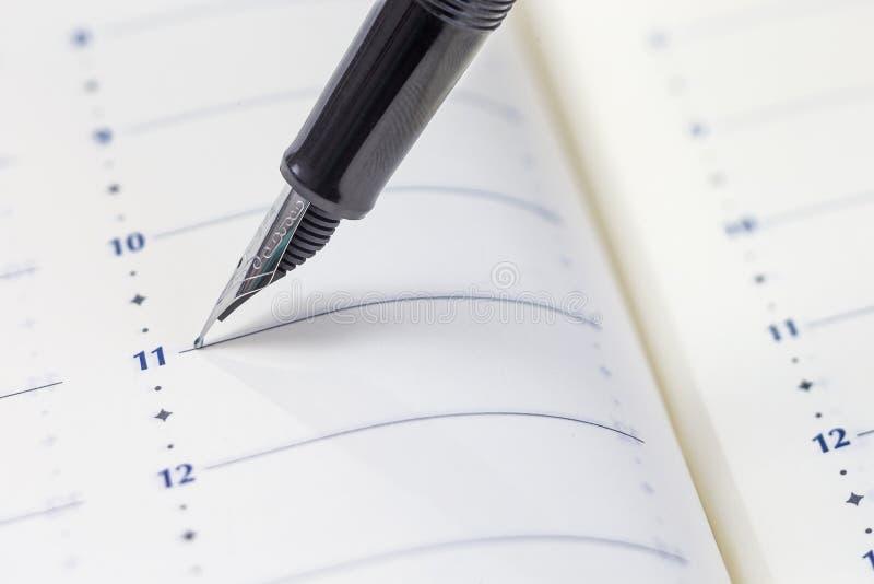 Penna alla pagina del calendario aspetti a writte qualcosa sul pianificatore immagini stock