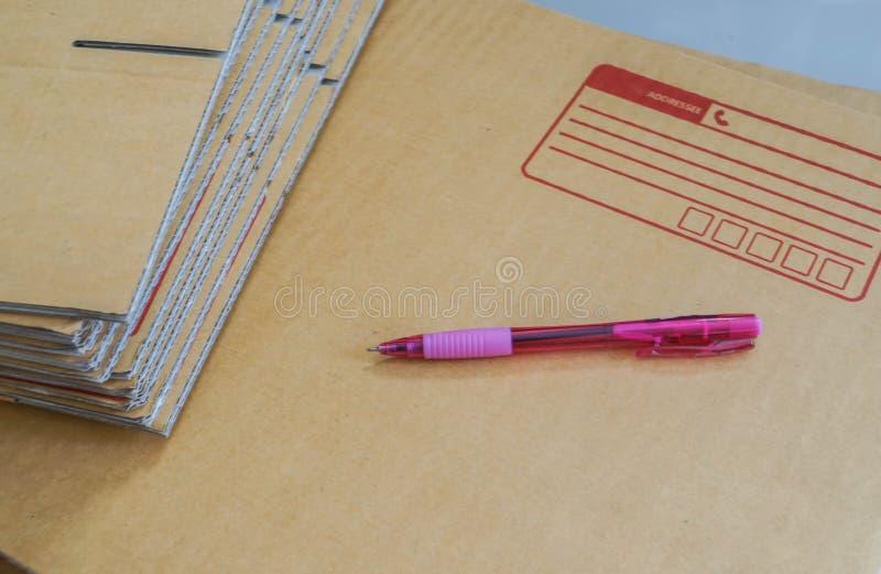 Penna alta vicina per la scrittura sulla scatola postale per la spedizione immagini stock