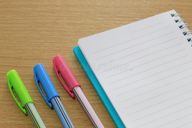 Penna in bianco di colore e del taccuino disposta su un pavimento di legno marrone fotografia stock
