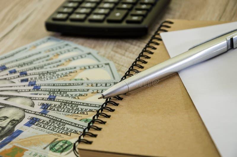 Penna, calcolatore, dollari di taccuino su fondo di legno, primo piano fotografia stock