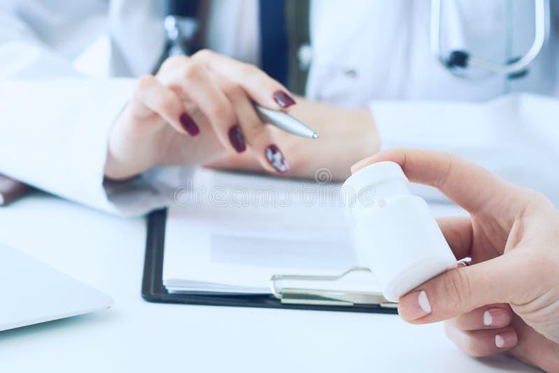 Penna d'argento e punti della medicina di medico della tenuta femminile della mano ad un barattolo della mano del ricoverato dell fotografia stock