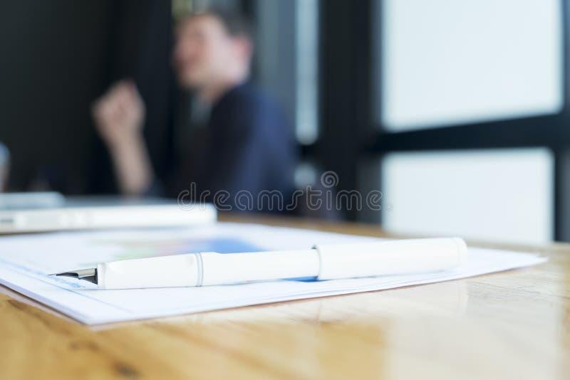 Penna del primo piano sulle mani funzionanti della sfuocatura e del grafico dell'uomo d'affari immagini stock