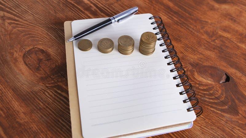 Penna del taccuino delle monete immagini stock