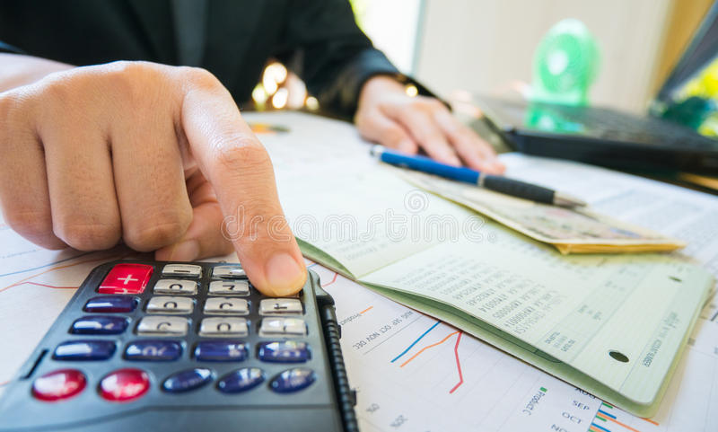 Penna della tenuta della mano della donna di affari e calcolatore di uso sulla dichiarazione o sul rapporto finanziario nel conce immagine stock