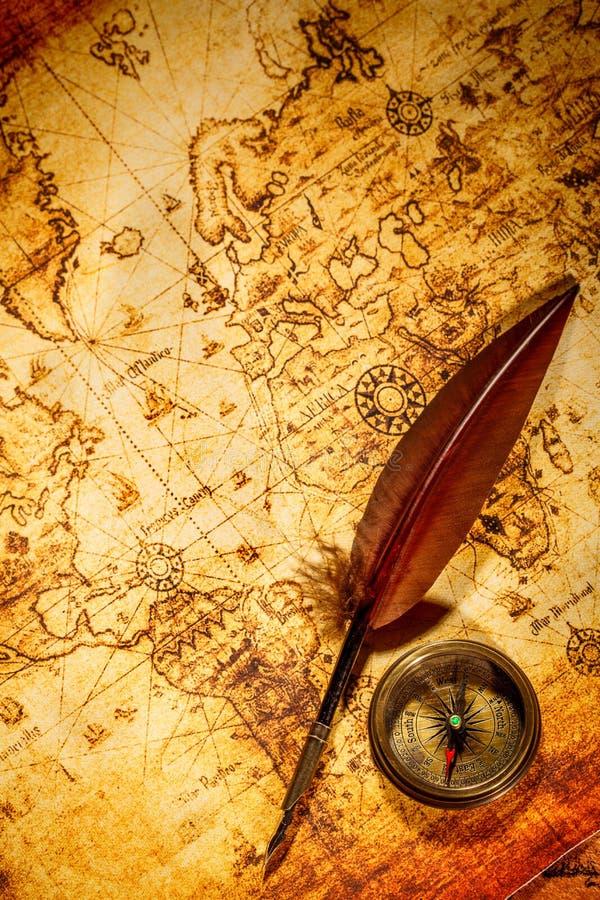 Penna di spoletta d'annata dell'oca e della bussola che si trova su una vecchia mappa. fotografia stock