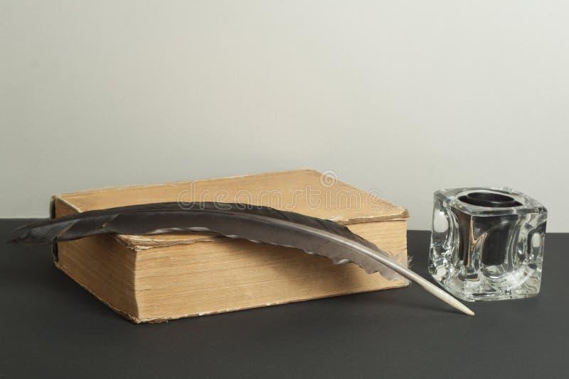 Penna di spoletta e del vecchio libro con il calamaio sulla tavola di legno Spazio della copia libera immagine stock