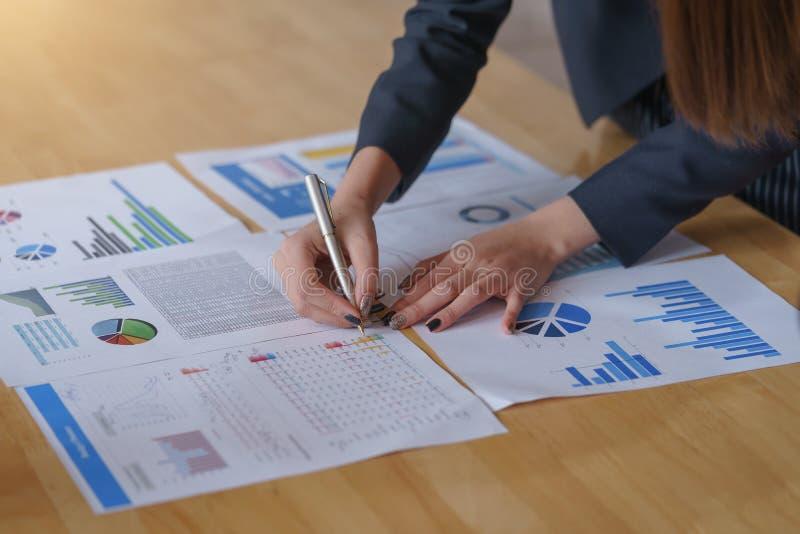 Penna di tenuta della donna di affari che indica sul documento di affari l'uso di analisi affinchè piani migliorino qualità a sal fotografie stock libere da diritti