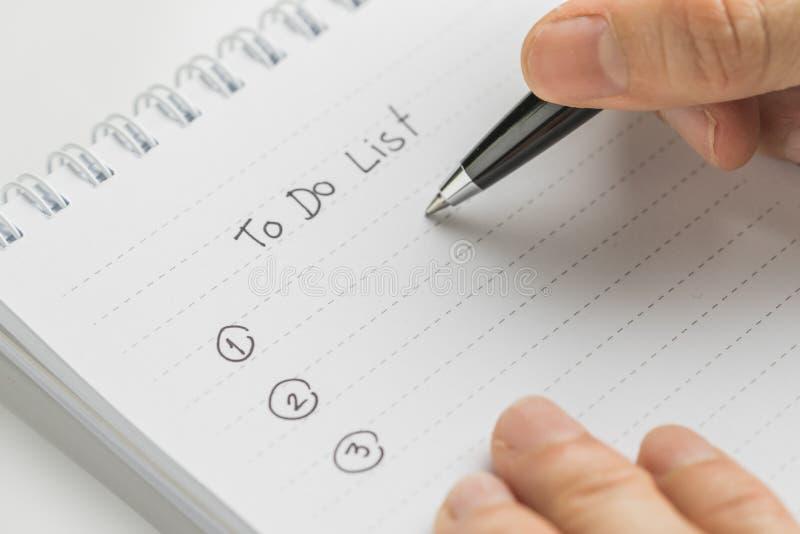 Penna di tenuta della mano che scrive che cosa fare in personale per fare il blocco note della lista sulla tavola bianca usando c fotografie stock libere da diritti