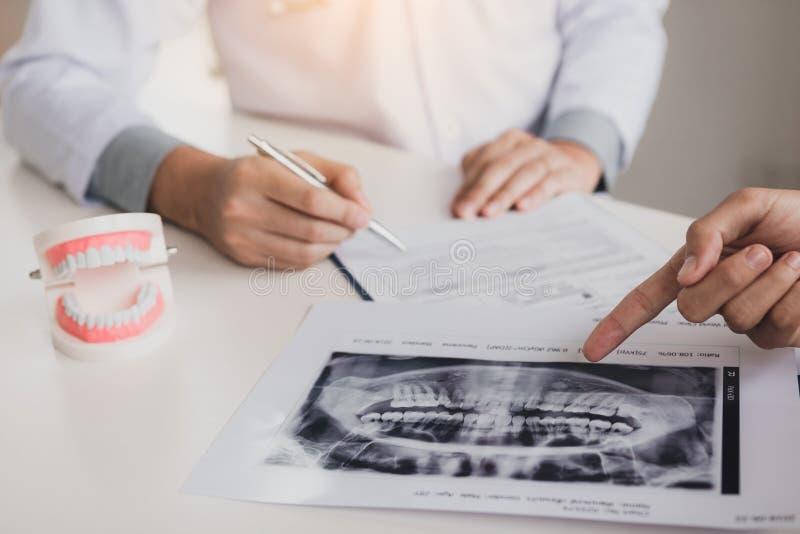 Penna di tenuta della mano del dentista e parlare con paziente con indicare l'immagine dei raggi x circa il trattamento della chi immagini stock