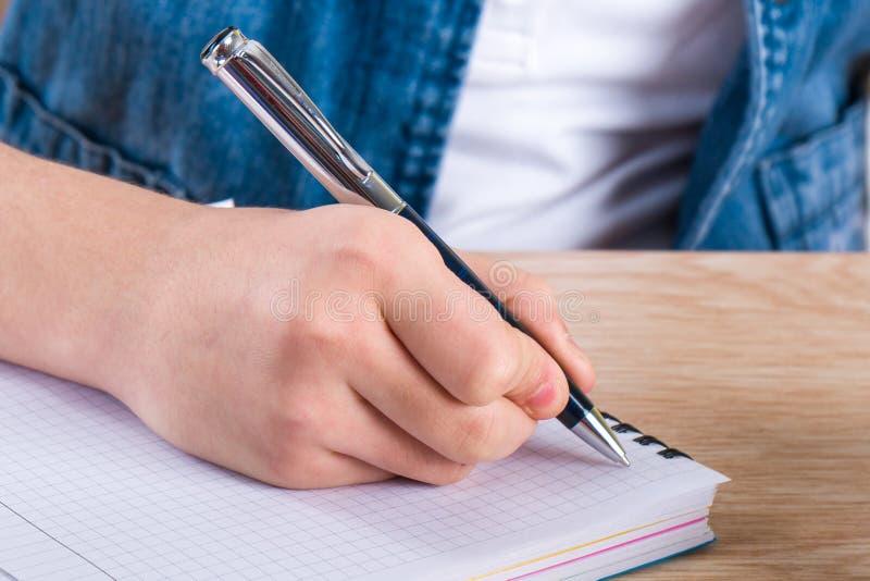 Penna di tenuta della mano del ` s del bambino Le lettere di scrittura del bambino in un noteboo immagine stock libera da diritti