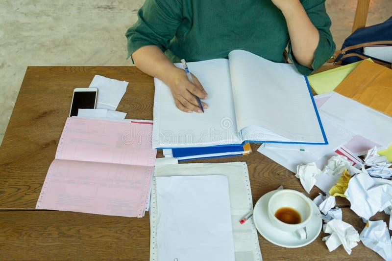 Penna di tenuta della mano della donna di affari che lavora dopo le ore con carta sgualcita sulla tavola immagini stock