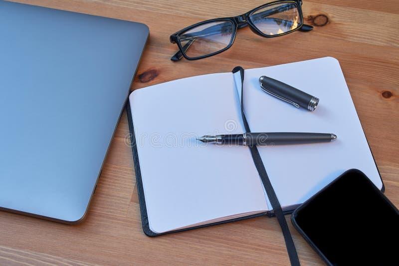 Penna di vetro, del taccuino e di scrittura del telefono cellulare del computer portatile del computer portatile di area di lavor fotografia stock