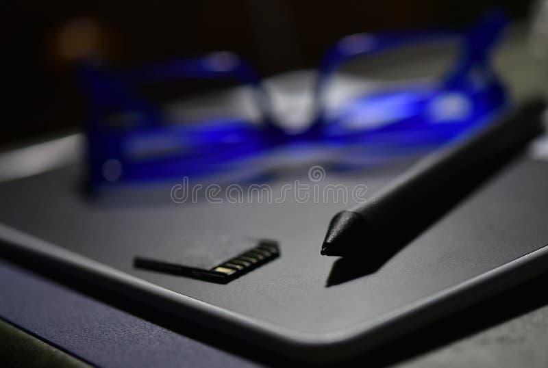 Penna e compresse, vetri dell'occhio azzurro e sfuocatura della scheda di memoria fotografie stock libere da diritti