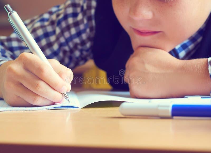 Penna e scrittura di tenuta caucasica del ragazzino in taccuino Fine in su fotografia stock