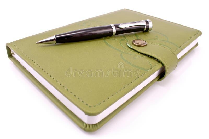 Penna e taccuino verde fotografie stock