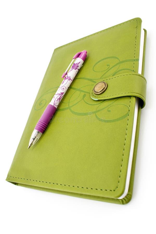 Penna e taccuino verde immagine stock
