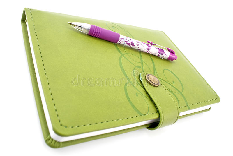 Penna e taccuino verde immagini stock
