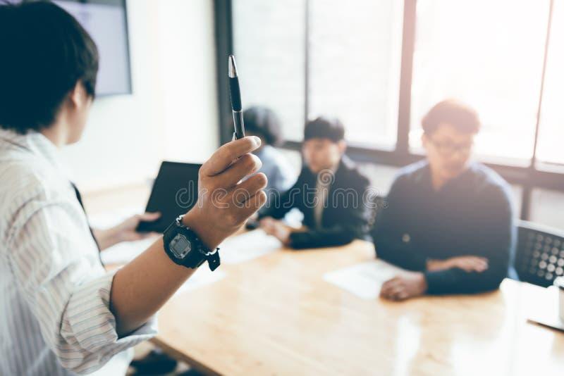 Penna ed insegnamento di tenuta dell'uomo d'affari con la riunione del personale nella b immagine stock