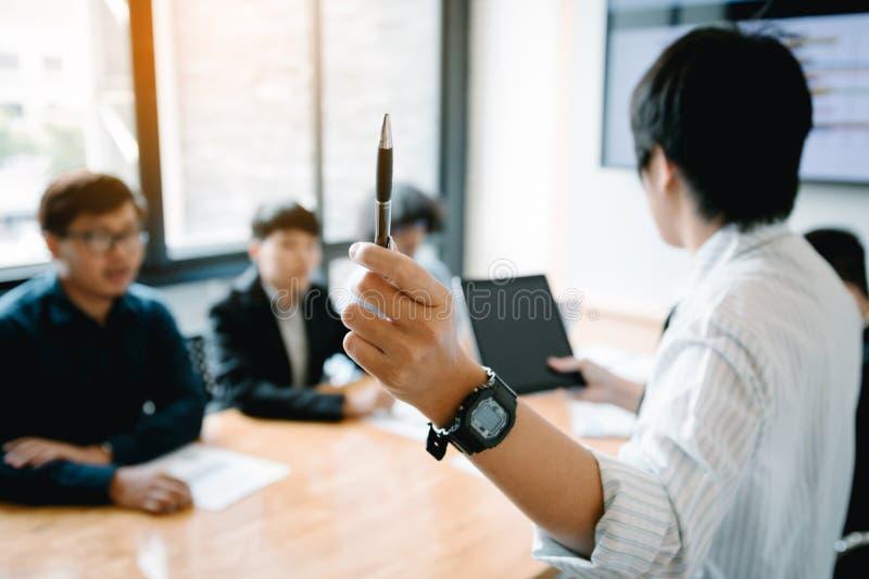 Penna ed insegnamento di tenuta dell'uomo d'affari con la riunione del personale nella sala del consiglio fotografie stock libere da diritti
