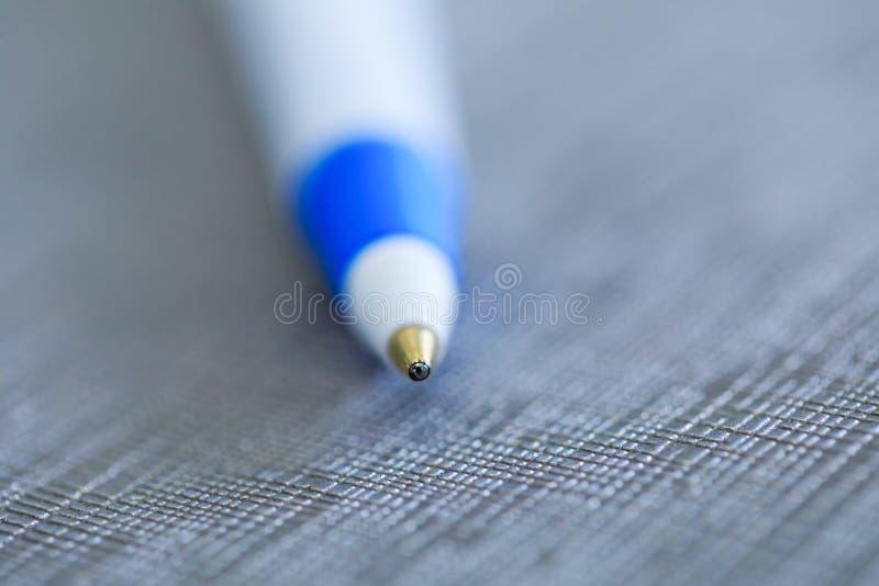 Penna för biro för bollpunkt i makrofototangent på utsmyckad bakgrund clos arkivbilder