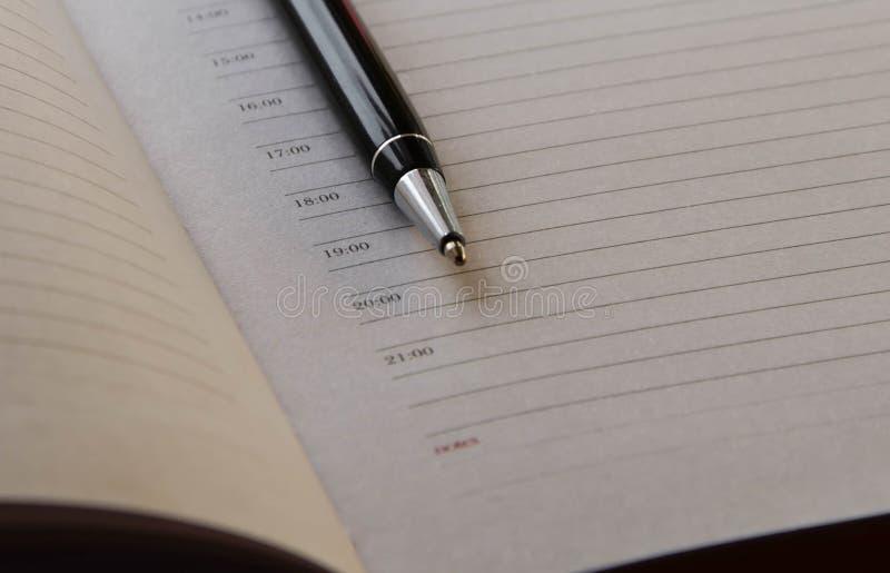 Penna för bollpunkt på bakgrunden av en tjock anteckningsbok arkivbild