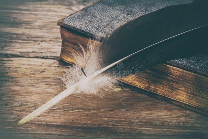 Penna för gammal bok och fjäder arkivfoto
